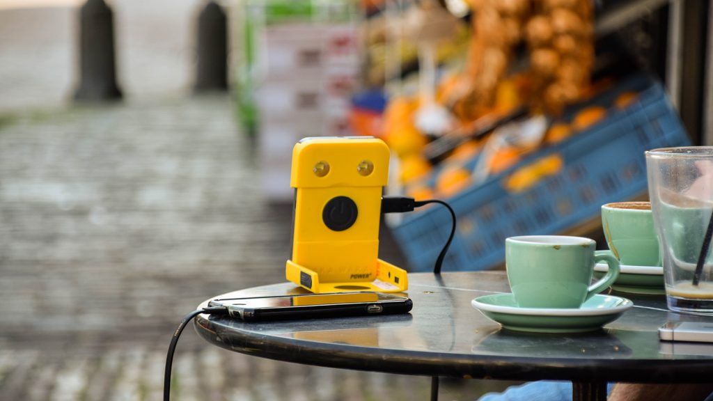 WWP+, yellow, usage, button side, with smartphone, city ©WakaWaka